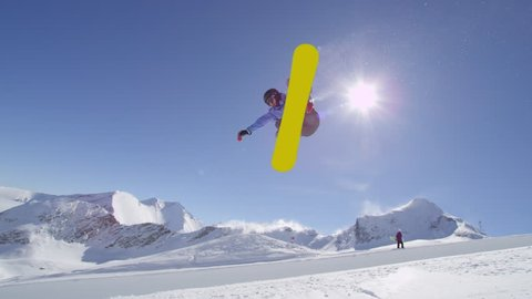 SLOW MOTION: Young pro snowboarder riding the half pipe in big mountain snow park, jumping high out of the halfpipe wall, performing tricks and rotations with grabs in sunny winter