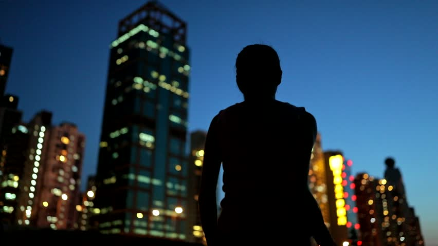 Slow motion of Silhouette excited woman holding shopping bags at sunset time with the building background   #30681049