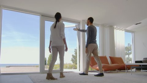 Beautiful Young Couple In Their Newly Purchased House, They Look at the Sea Through Floor to Ceiling Windows. Their Luxury Home is Bright, Modern with Tastefully Made Interior. 4K UHD.