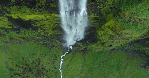 Aerial tilt of tall waterfall in tropical landscape