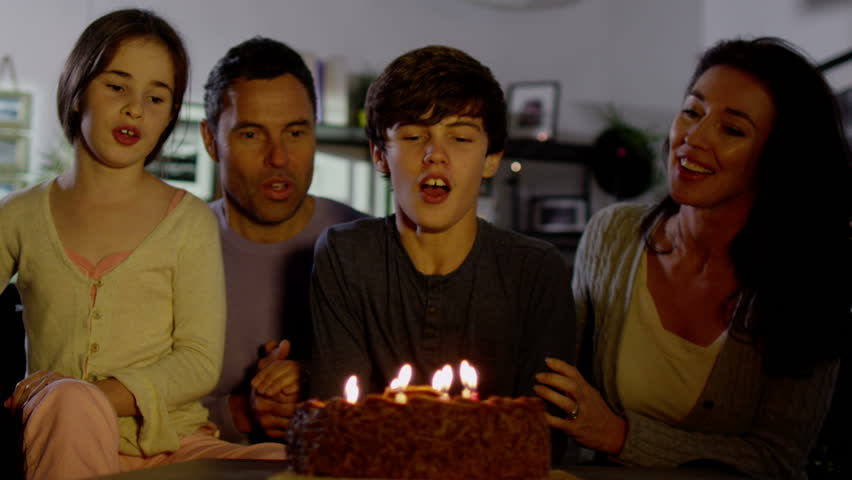 A young boy blows out the candles on his birthday cake while the rest of his family cheer and clap. In slow motion.