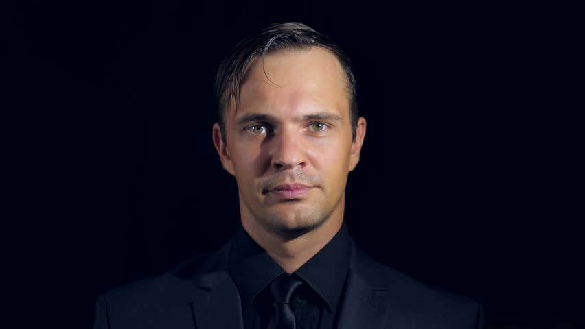 closeup of a man in black clothes on black background. 4k. Slow motion. man looks at the camera and blinks