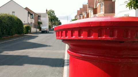 Point of view shot, hiding behind a classic red British Post Office post box.