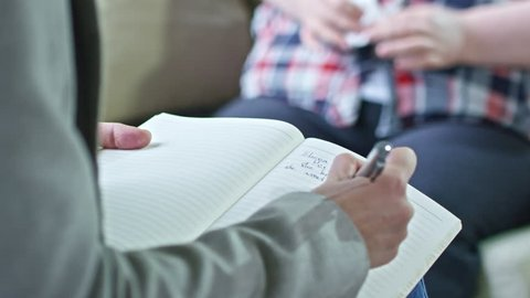 PAN with close up of hands of female psychiatrist writing notes in notebook as unrecognizable obese patient with handkerchief sitting in background