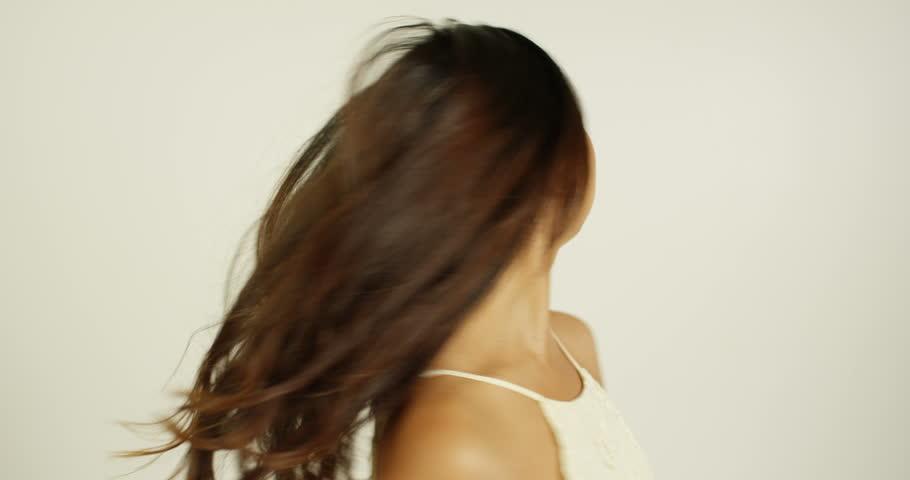 4K Beautiful Asian model smiling & posing against white backdrop in studio photoshoot. Slow motion.