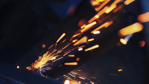 Craftsman sawing metal with disk grinder in workshop. Slow Motion. Flies of spark from hot metal.