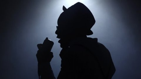 Singer approaching the microphone in smoke and white light. Black background. Silhouette. Slow motion. Close up