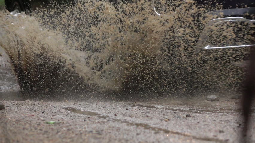 SLOW MOTION CLOSE UP: Detail of a SUV car tyre driving over deep puddle and splashing water across the dirt road. Black SUV car tires driving on wet dirt road after rain and over muddy puddle. #30789142