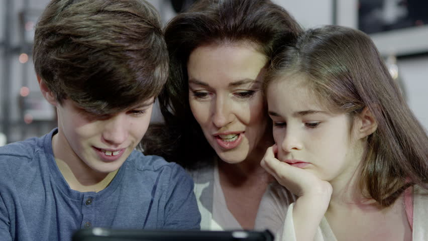 An attractive mother is spending time at home with her two adolescent children. They are looking at the screen of a tablet computer then something on screen makes them all laugh. In slow motion.