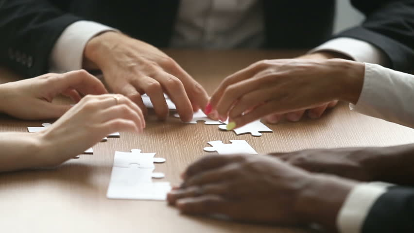 Multiracial business people hands unsuccessfully trying to assemble jigsaw puzzle at office table, team making incorrect decisions, finding wrong solutions in bad teamwork concept, close up view