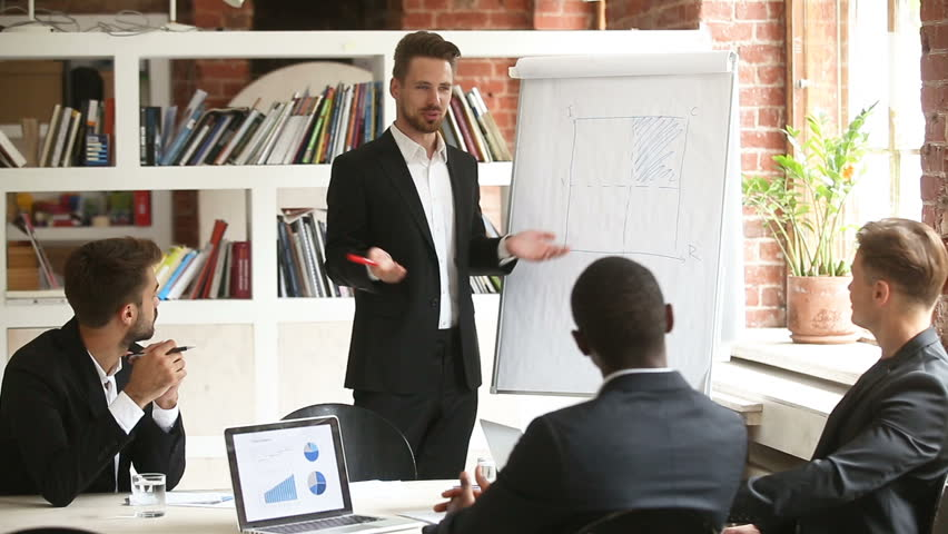 Businessman presenting new project to diverse partners with flip chart, team leader giving presentation to multiracial colleagues in boardroom, corporate business training, making offer to investors