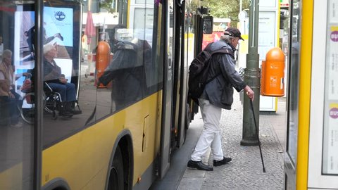 BERLIN, GERMANY - SEP 10, 2017: Public transport in Berlin on a bus stop disabled senior man with stick walks out of bus