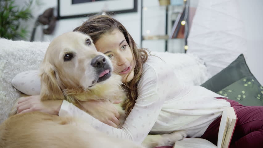 Attractive young woman at home is stroking and snuggling with her pet dog. In slow motion.