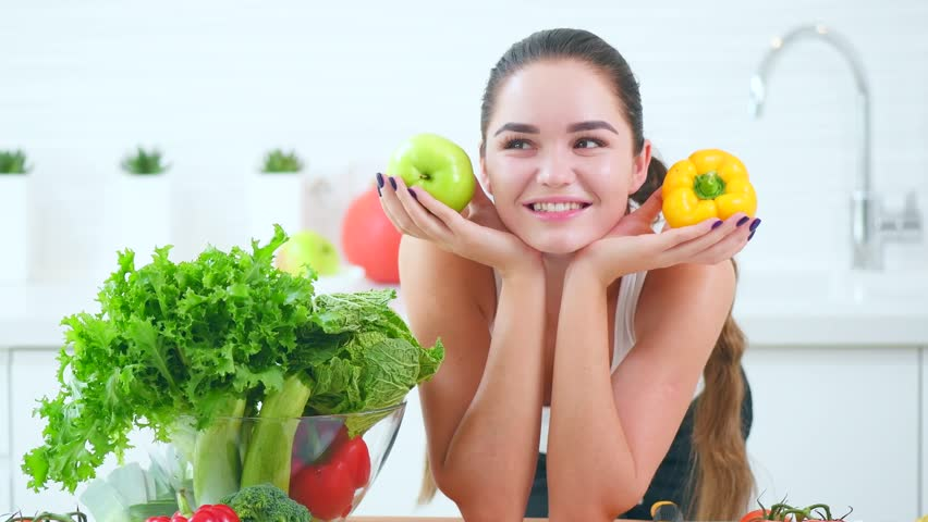 Beauty Young Woman Holding Fresh Vegetables And Fruits Smiling In Her Kitchen At Home