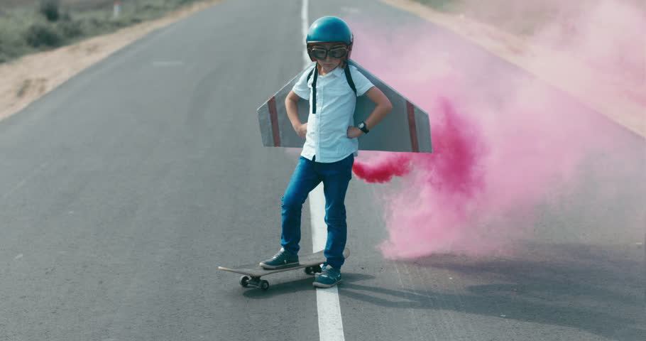 CINEMAGRAPH - seamless loop. Little boy wearing helmet and styrofoam wings standing on a skateboard on a rural road, pretending to be a pilot | Shutterstock Video #30860722