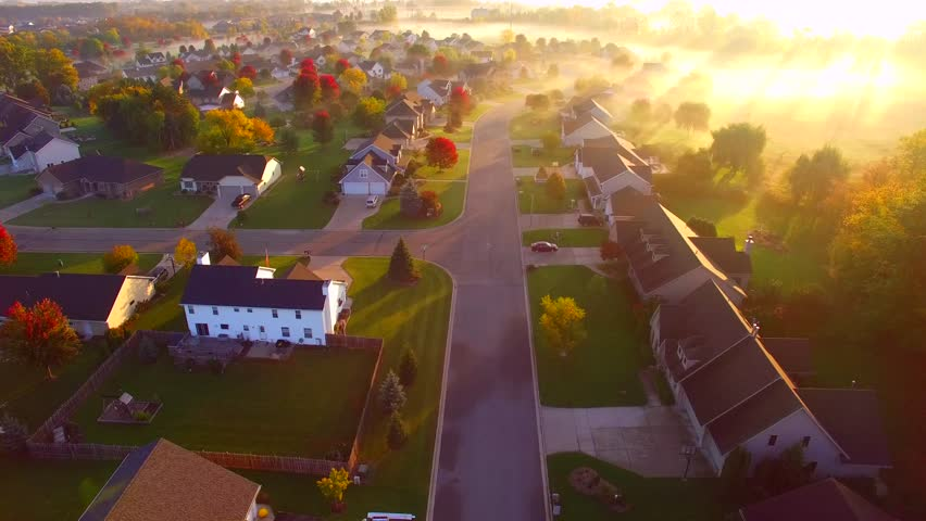 Tranquil idyllic Autumn neighborhood houses shrouded in fog at daybreak, Fall colors, aerial flyover.