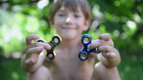 Boy playing with two fidget spinner stress relieving toys outdoor
