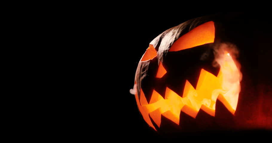 Scary carved halloween pumpkin in hot burning hell fire flames. The big helloween pumpkin has a mad face with glowing eyes and also a smoke in its mouth and teeth.