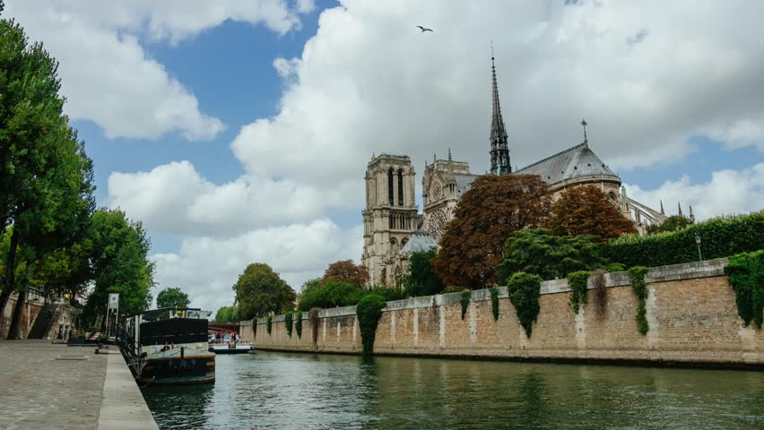 Time lapse of cathedral Notre-Dame de Paris on a summer day with clouds, touristic boats on the Seine river, people walking on the quays. Famous touristic places, popular travel destinations in Europe | Shutterstock HD Video #30890005