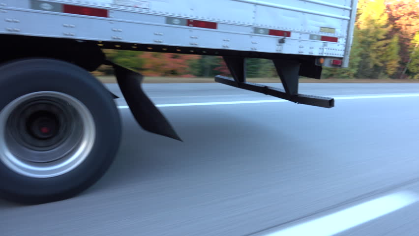 CLOSE UP: White freight semi truck passing by on highway. Detail of truck's wheels and tires rolling on dry freeway asphalt. 18 wheeler transporting cargo, tyres spinning fast along the motorway #30893182