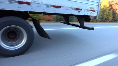 CLOSE UP: White freight semi truck passing by on highway. Detail of truck's wheels and tires rolling on dry freeway asphalt. 18 wheeler transporting cargo, tyres spinning fast along the motorway