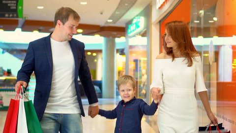 Family walking through shopping mall carrying sale bags.Shot on Canon 5D MkII at frame rate of 25fps