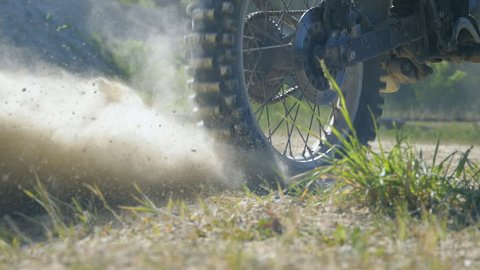 Wheel of motocross bike starting to spin and kicking up ground or dirt. Motorcycle starts the movement. Slow motion Close up