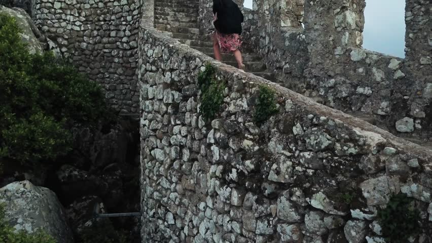 Climbing steps of Castle of the Moors Sintra, Portugal. Aerial footage running up a castle wall. 4k footage Pena National Park with castle in a forest. Fairytale castle video with a palace background.