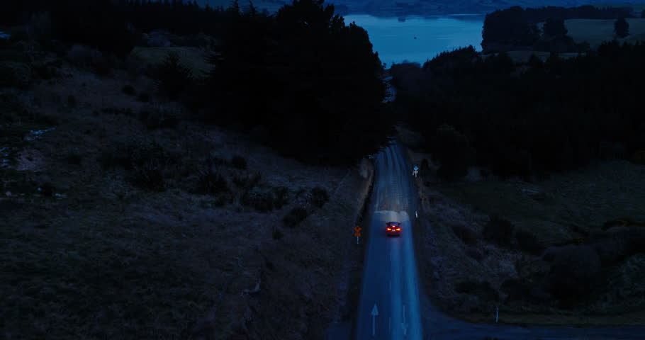 Aerial view car driving on country road at dusk through dark forest with headlights