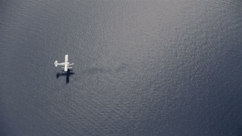 View from airplane of float plane on lake water approaching and landing