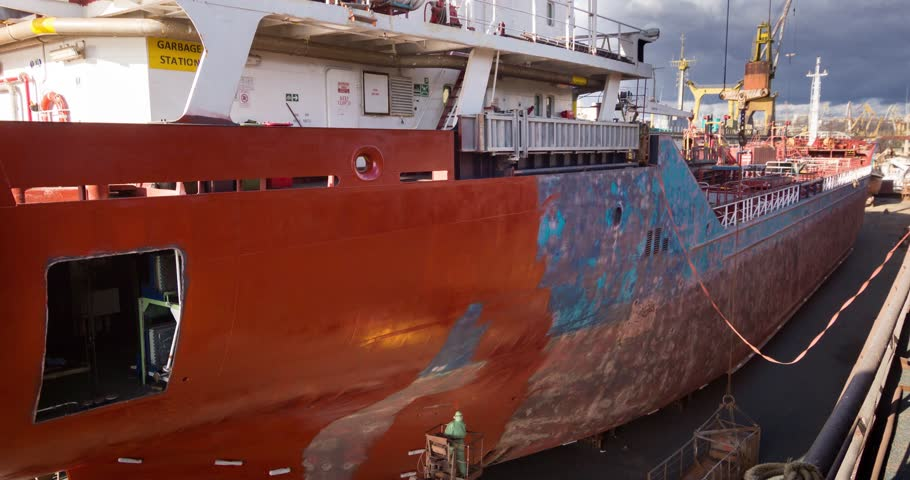 Workers repair and paint vessel at floating dock at the shipyard. Ship painters at work. Boat dyeing timelapse 4k video.
