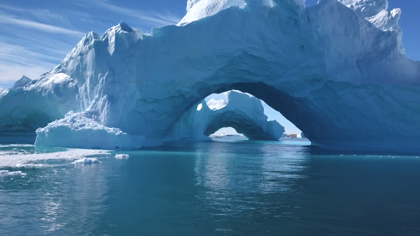 Aerial - Fly through the arch of a big iceberg with a second arch in background
