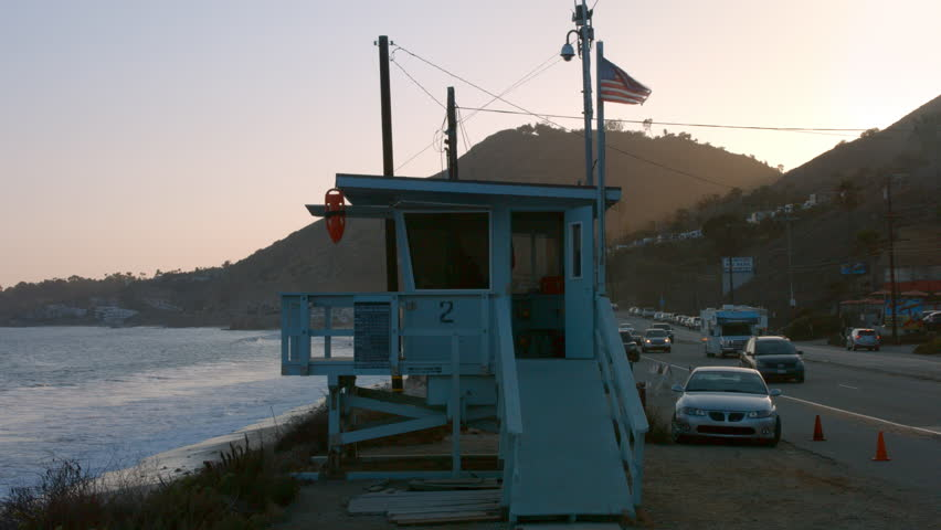 Lifeguard tower on the beach in front of a beautiful sunset and ocean waves on Pacific Coast Highway at Malibu, Los Angeles, California.. | Shutterstock HD Video #30951088