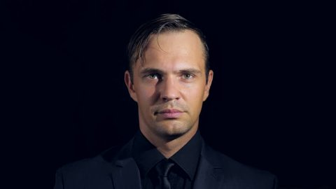 super close-up of a man in black clothes on a black background. 4k. Slow motion. man points finger at the camera.