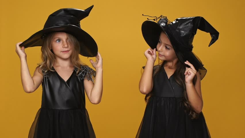 Two little girls witches in black dresses and hats looking at each other  while standing isolated over orange d1da8e3b56b1