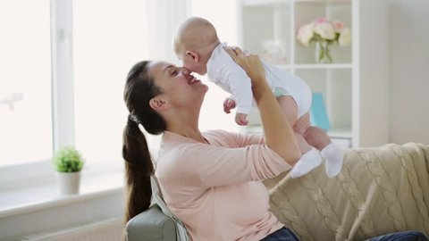 motherhood, family and parenthood concept - happy smiling young mother with little baby at home