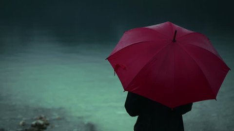 Lonely woman with red umbrella standing on lakeshore in rain on a cold autumn day. Loneliness and solitude concept.