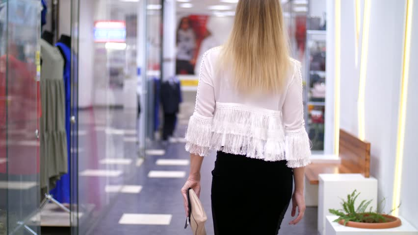 Sexy girl, tall, beautiful blond woman walking down the hall of shopping center, along the windows of shops and stylish boutiques. Shopping in a stylish clothing stores. | Shutterstock HD Video #30985432