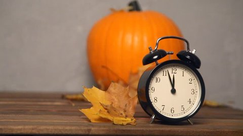 Halloween seasonal pumpkin and alarm clock on wooden table and grey background