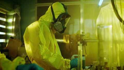 In the Underground Drug Laboratory Clandestine Chemists Wearing Protective Masks and Coveralls Mix Chemicals. One Pours Liquid From Canister into Bowl, Second Checks Beaker for Product Consistency.