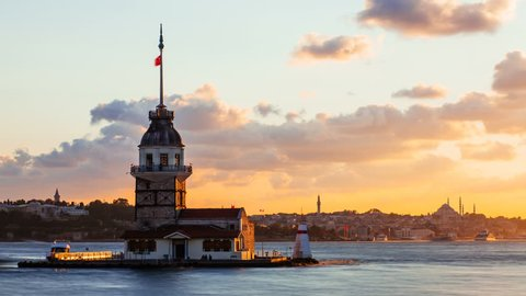 Timelapse of Maiden Tower or Kiz Kulesi with floating tourist boats on Bosphorus in Istanbul at sunset