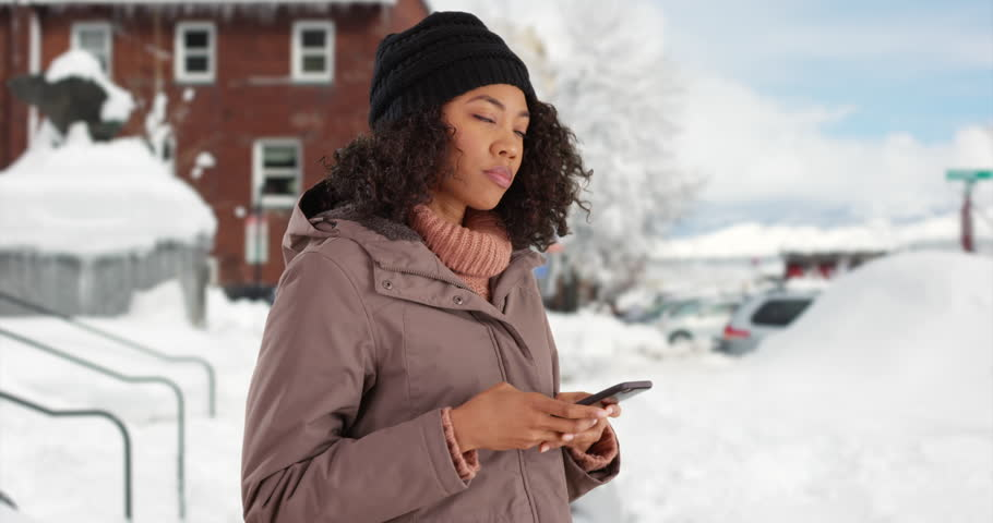 Pretty African American female removes gloves to text on cell phone outside in the snow. Cute black woman in winter coat messaging on mobile device in outdoor setting. 4k | Shutterstock HD Video #31014679