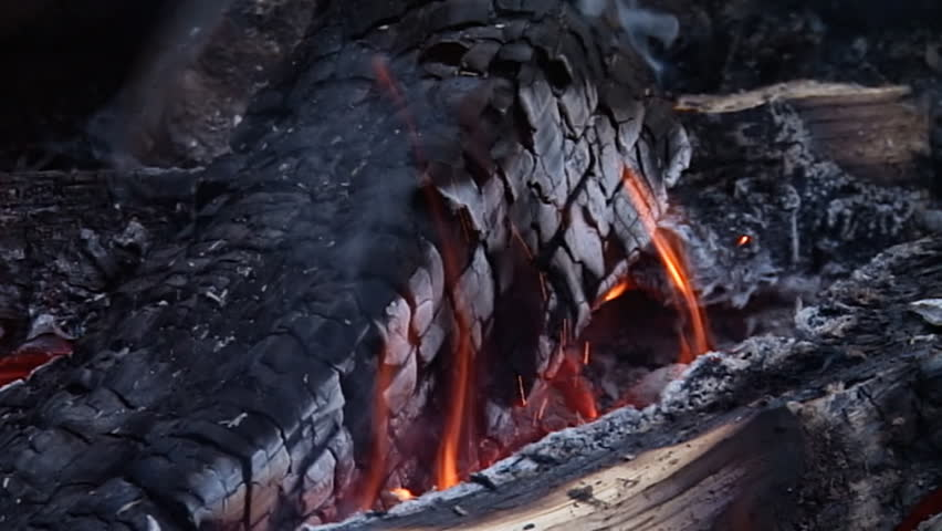 Tight shot of burning logs with smoke and flames in a campfire. Shot at 240fps,