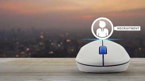 Businessman and magnifying glass icon with wireless computer mouse on wooden table over blur of cityscape on warm light sundown, Recruitment online concept