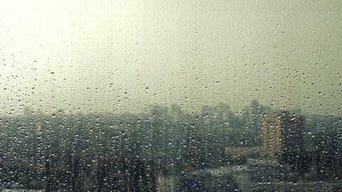 Rain drops on window glass and blurry city skyline on background