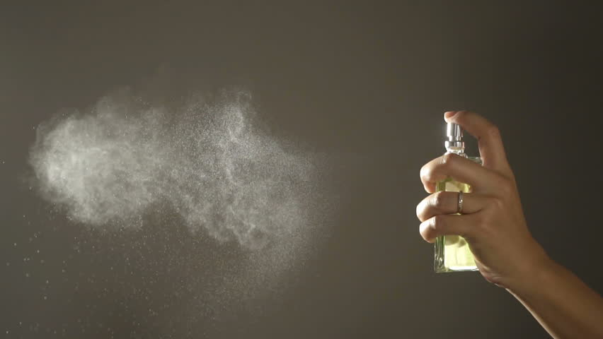Slow motion,Woman spraying fragrance with scent particles.
