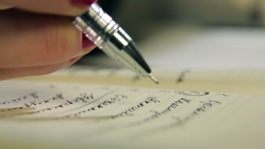 Woman writes a pen in daily