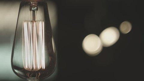 Vintage lamp light. Classic edison light bulb in room. Close up of vintage lightbulb indoors. Decorative antique style light bulb on dark background