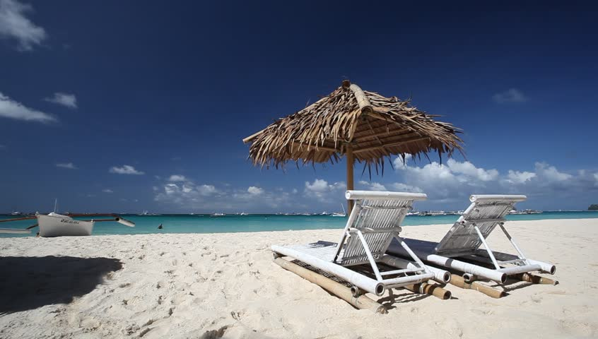 Sun umbrella and sunlongers on sandy tropical beach with white sand and turquoise sea water