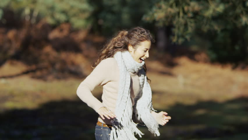 Attractive couple chasing each other through the woods having fun, playing and laughing. In slow motion